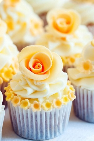 Cupcakes decorated with yellow sugar roses